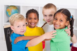 a group of little preschool friends hugging in a circle in classroom